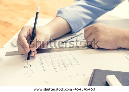 architect drawing architectural project on blueprint, engineering concept, architecture concept, soft focus, vintage tone #454545463