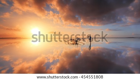 Photographer is taking a picture of sunrise at beach with beautiful sky reflections