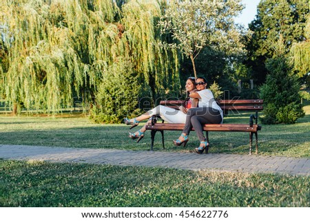 Happy mom and daughter embracing on a bench in the park #454622776