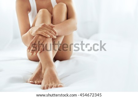 Woman Body Care. Close Up Of Long Female Legs With Perfect Smooth Soft Skin, Pedicure And Beautiful Hands With Natural Manicure, Healthy Nails On White Bed. Epilation, Beauty And Health Concepts #454672345
