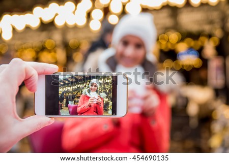 A beautiful young woman smiling in to a phone for a picture on the christmas market. #454690135