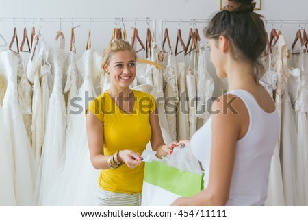 Woman buying wedding dress in clothes shop. paying with credit card #454711111
