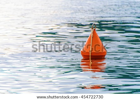 Red buoy on the sea waves background Royalty-Free Stock Photo #454722730