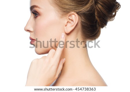 health, people and beauty concept - beautiful young woman pointing finger to her ear over white background Royalty-Free Stock Photo #454738363