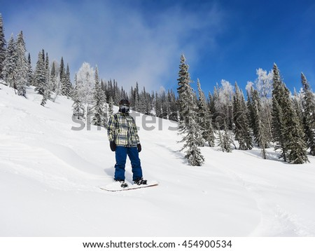 A snowboarder stands on a steep mountain slope on a clear Sunny day. looking at the camera #454900534