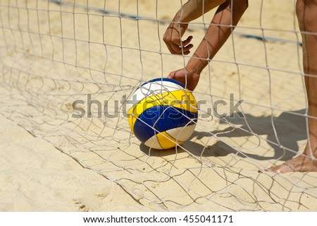Beach volley ball: man picks up a ball #455041171