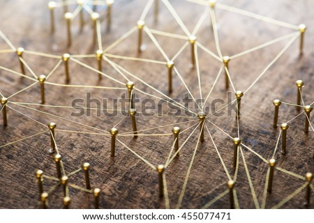 Linking entities. Network, networking, social media, internet communication abstract. Many small network connected to a larger network. Web of gold wires on rustic wood. . Shallow Depth of field. #455077471