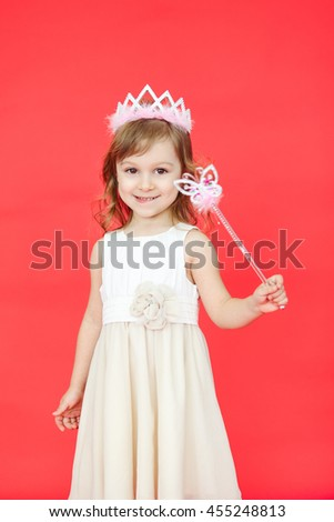 Vertical portrait of beautiful girl dressed in fairy isolated on red background. Cute little kid wearing a crown and white dress holding a magic wand. #455248813