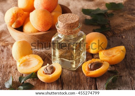 apricot kernel oil in a glass jar closeup on the table and ingredients. Horizontal Royalty-Free Stock Photo #455274799