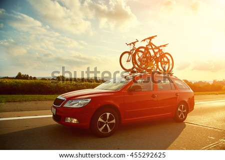 car is transporting bicycles on the roof. bikes on the trunk #455292625