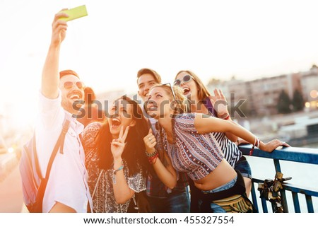 Happy young people taking selfies in city