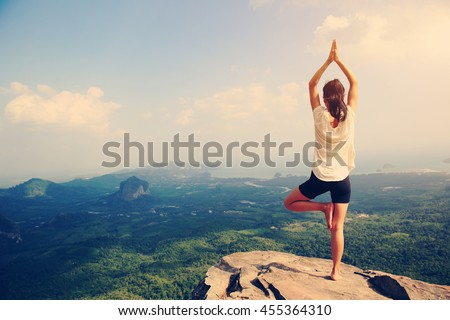young fitness woman practice yoga at mountain peak cliff #455364310