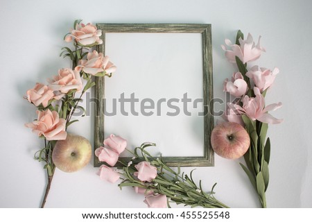 Wooden photo frame, apple and pink roses on watercolor paper. Flat lay table with gentle floral ornament. Wedding background. Pastel flowers on white backdrop. Horizontal composition with text place
