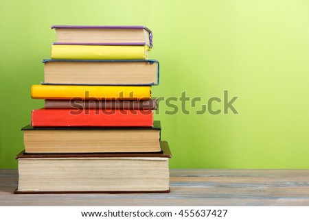 Stack of colorful books, grungy green background, free copy space Vintage old hardback books on wooden shelf on the deck table, no labels, blank spine. Back to school. Education background #455637427