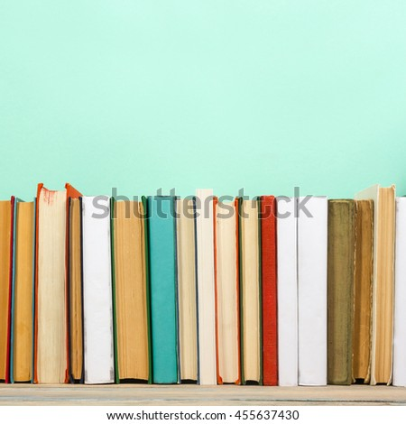 Stack of colorful books, mint green background, free copy space Vintage old hardback books on wooden shelf on the deck table, no labels, blank spine. Back to school. Education green background #455637430