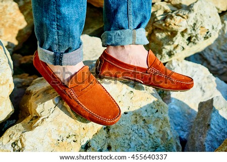 Close up on man's legs wearing red loafers or moccasins on a rocky background in the sun, model posing #455640337