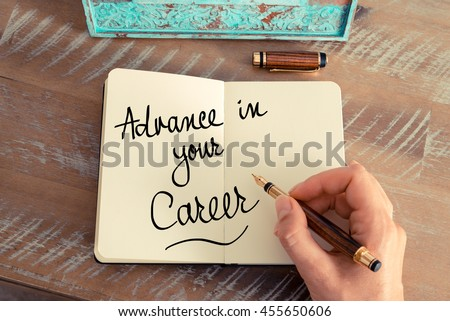 Handwritten text Advance In Your Career as business concept image. Retro effect and toned image of a woman hand writing a note with fountain pen on a notebook. #455650606