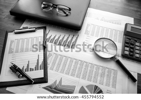 Business accessories (notebook, calculator, planchette, tablet, fountain pen, glasses) and graphics, tables, charts on white sheets on office desk. Soft focus. Black and white. #455794552