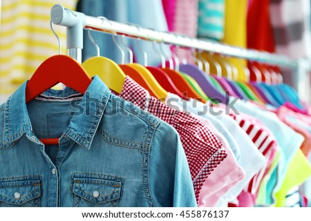 Children clothes hanging on hangers in the shop Royalty-Free Stock Photo #455876137