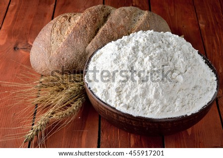 Flour, bread and ears on the wooden table. Flour in a clay bowl, rural style. #455917201
