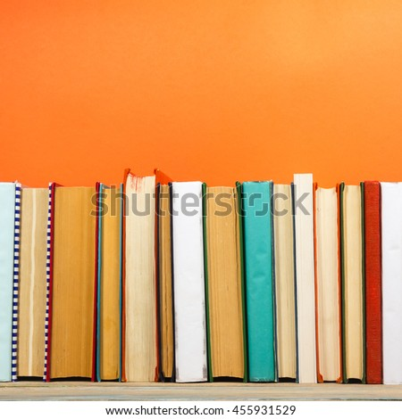 Stack of colorful books, grungy orange background, free copy space Vintage old hardback books on wooden shelf on the deck table, no labels, blank spine. Back to school. Education orange background #455931529