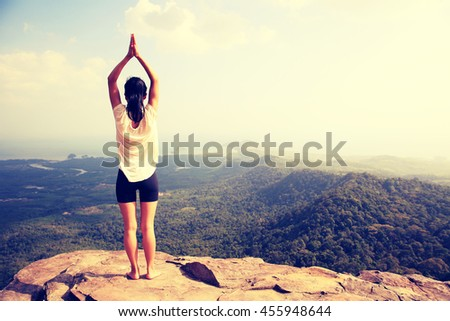 young fitness woman practice yoga at mountain peak cliff #455948644