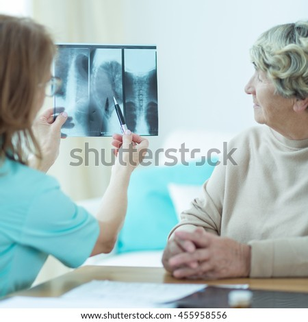 Image of doctor analysing x ray photography of elderly patient #455958556