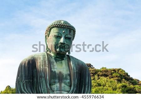Medium shot from side of big bronze Buddha in Kamakura, Japan, on a blue sky. #455976634