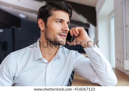 Attractive young businessman sitting and talking on mobile phone sitting indoors in cafe #456067123