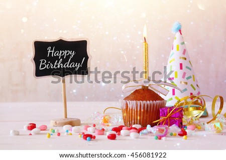 Birthday concept with cupcake and candle next to little chalkboard on wooden table. Glitter overlay