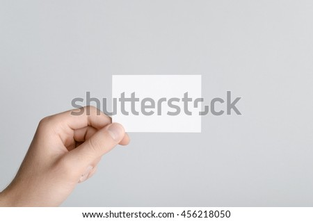 Business Card Mock-Up (85x55mm) - Male hands holding a blank card on a gray background.