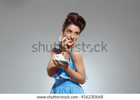 Picture of beautiful pin-up girl eating cake at studio