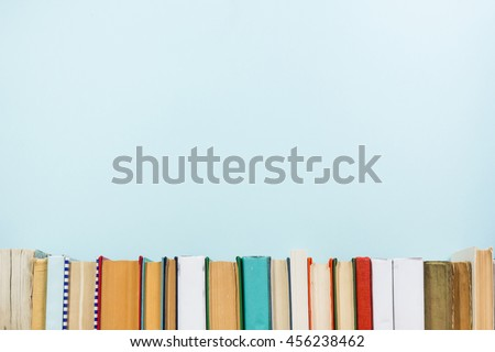 Stack of colorful books, grungy blue background, free copy space Vintage old hardback books on wooden shelf on the deck table, no labels, blank spine. Back to school. Education background #456238462