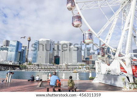 People enjoy sitting at the Darling Harbour with part of Ferris Wheel Royalty-Free Stock Photo #456311359