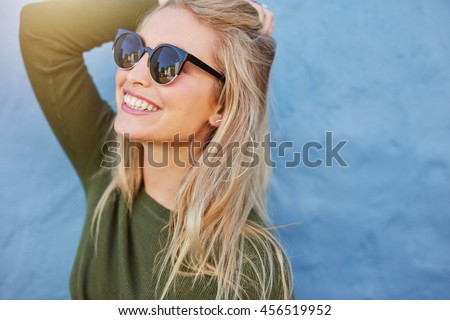 Cheerful young woman in sunglasses against blue background. Beautiful female model with long hair. #456519952