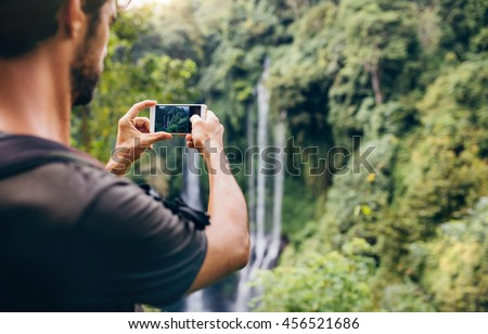 Close up of a man taking photos of waterfall with his cellphone. Male hiker photographing a water fall in forest.
