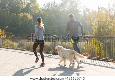 fitness, sport, people and jogging concept - close up of couple with dog running outdoors #456620743