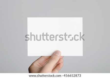 A6 Flyer / Postcard / Invitation Mock-Up - Male hands holding a blank flyer on a gray background. Royalty-Free Stock Photo #456652873
