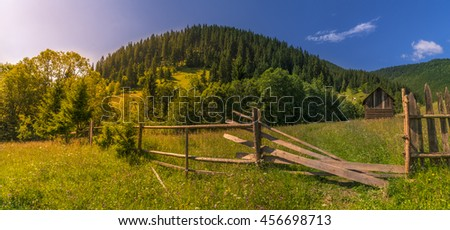 Sunny day in the Carpathians mountains - Rustic landscape with the wooded Carpathians mountains, a flowery meadow and a wooden fence with its gate open toward and old barn.  #456698713