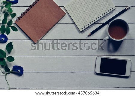 Office stuff and it gadgets display on top view business desk with copy space at text of picture. Filter effect vintage tone film. Creative table, modern project