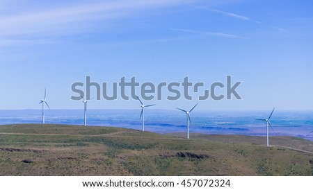 Low angle view group of wind turbines towers again cloud blue sky on a wind farm at Ellensburg, Washington, US. Clean, sustainable, renewable energy concept. Alternative energy source from wind power. #457072324