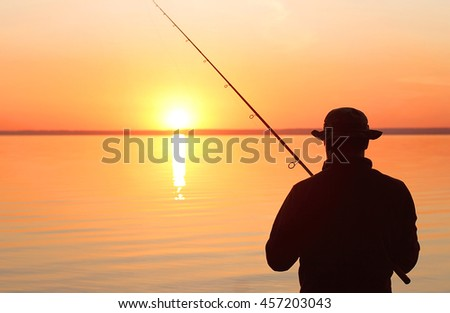Fisherman fishing with spinning rod on a river bank at sunrise #457203043