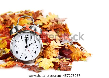 Alarm clock in colorful autumn leaves isolated against a white background with light shadow and shallow depth of field. Daylight savings time concept. #457275037