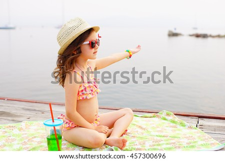 little girl in red sunglasses and bathing suit with sparkling water sunning at the pier at the lake #457300696