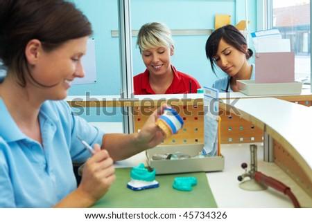 Three dental technicians working in a dental laboratory #45734326