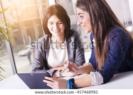 Young successful business women discussing and sharing ideas, using tablet in bright modern office. Focus on girl on the right. Lens flare effect