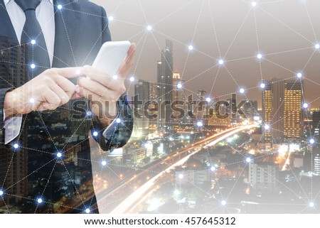 Double exposure of professional businessman using smart phone and network connection with blurred cityscape in communication , technology and business concept #457645312