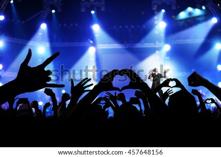 Silhouette of a crowd of cheering fans during a live concert, live music concert #457648156