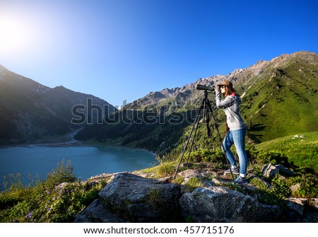 Tourist woman with hat watching trough spyglass on the lake in the mountain #457715176