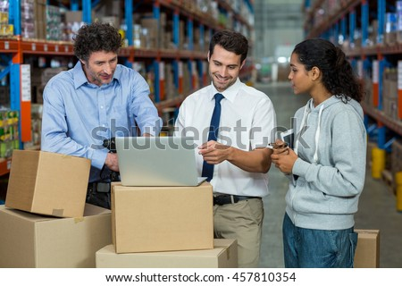 Worker team looking a laptop put on a cardboard box in a warehouse #457810354